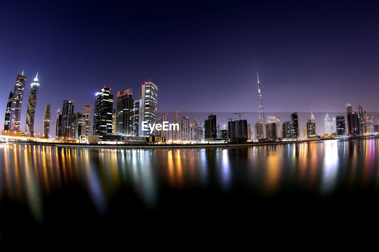Low Angle View Of Illuminated City Reflecting In River Against Clear Sky