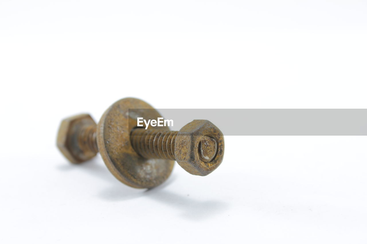 Close-Up Of Rusty Nut Bolt Against White Background