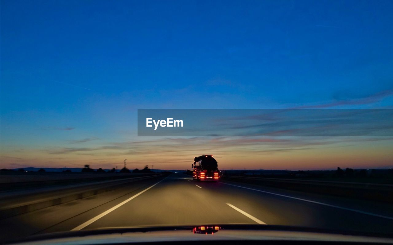 Vehicle on highway against sky during sunset