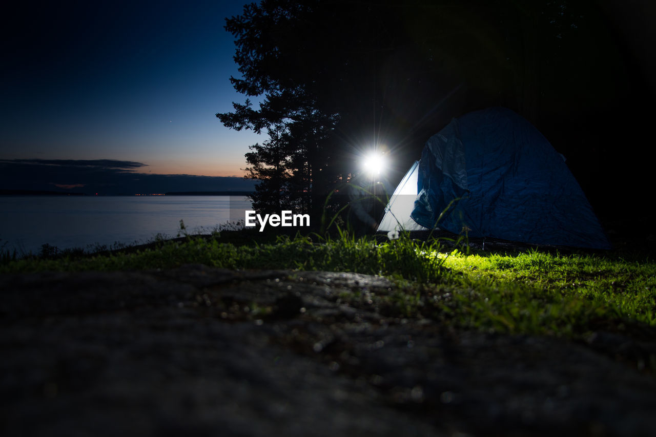 Woman Camping On Field At Night