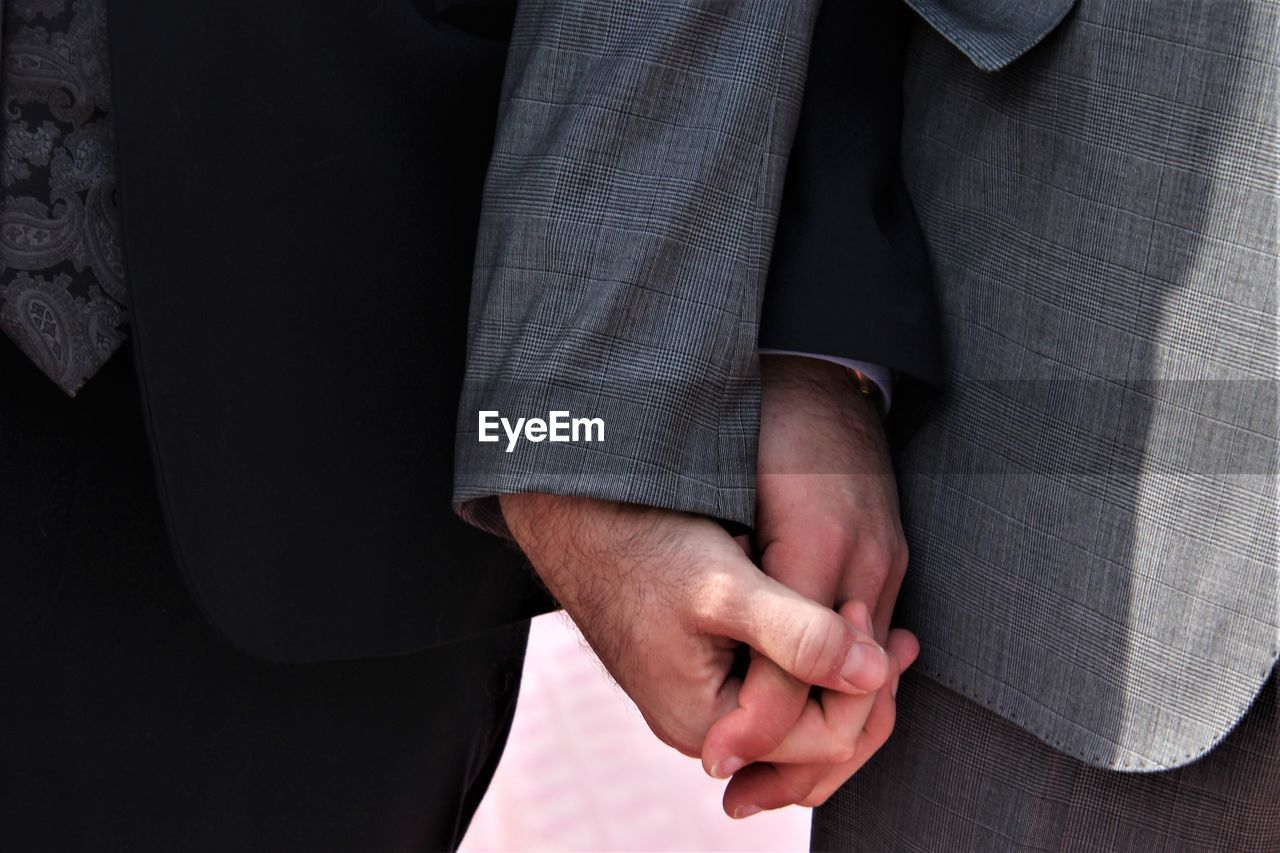 Midsection of men holding hands