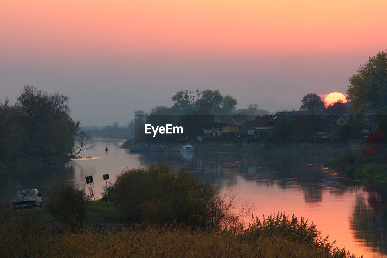 water, plant, sky, tree, scenics - nature, beauty in nature, sunset, lake, tranquility, tranquil scene, nature, reflection, no people, orange color, idyllic, fog, outdoors, non-urban scene, waterfront