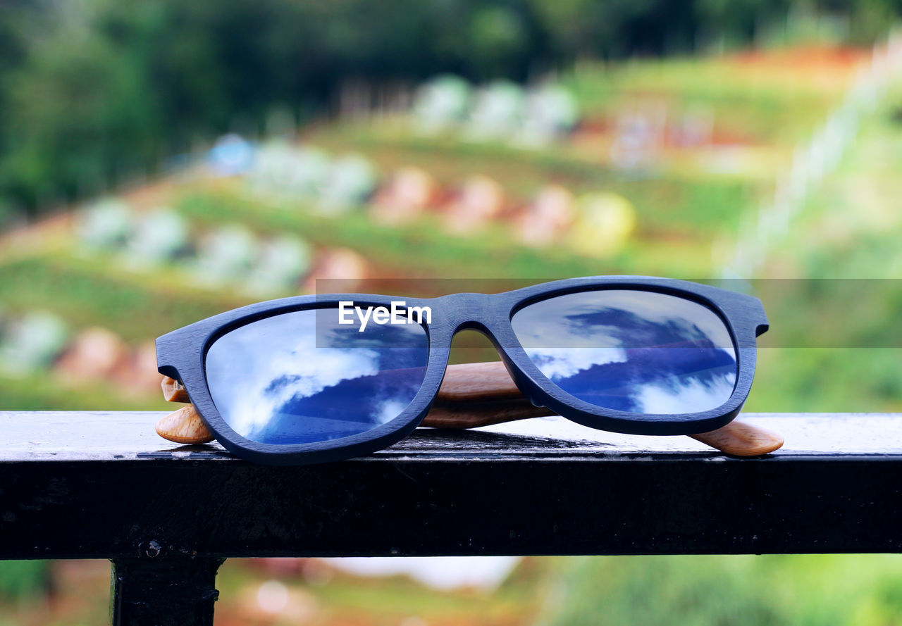 focus on foreground, glasses, sunglasses, fashion, reflection, close-up, day, personal accessory, security, glass - material, protection, transparent, nature, outdoors, eyeglasses, railing, safety, sunlight, no people, still life, eyewear
