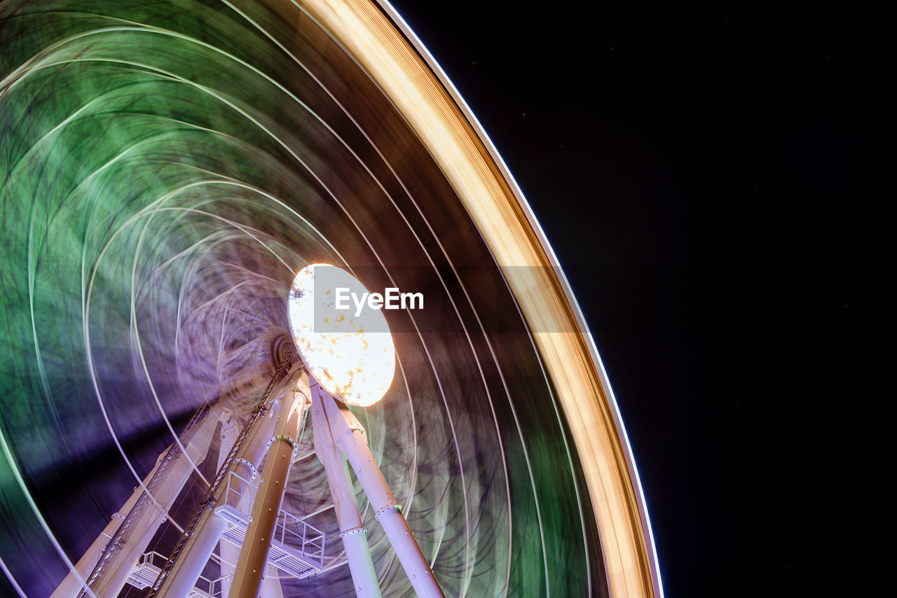 Low Angle View Of Illuminated Ferris Wheel Against Clear Sky At Night
