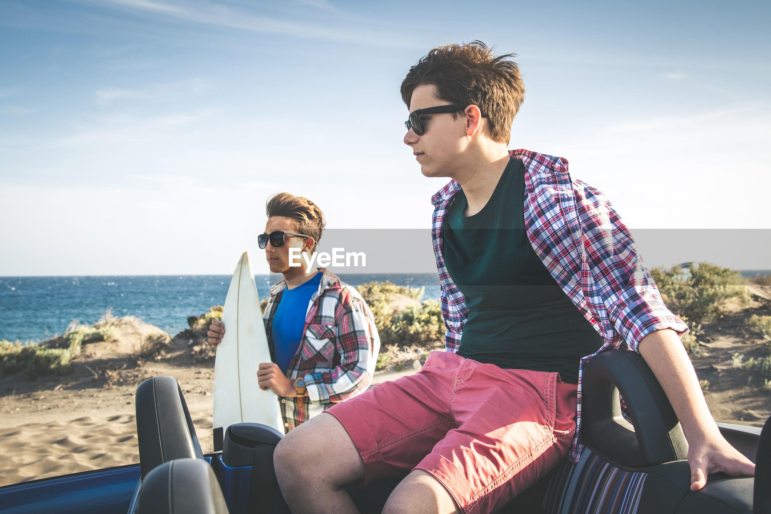 Teenage boys by car at beach against sky
