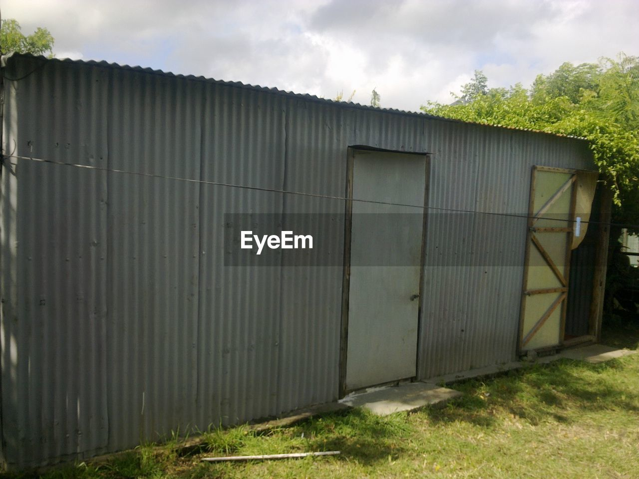 day, built structure, outdoors, no people, building exterior, architecture, corrugated iron, grass, industry, sky, factory