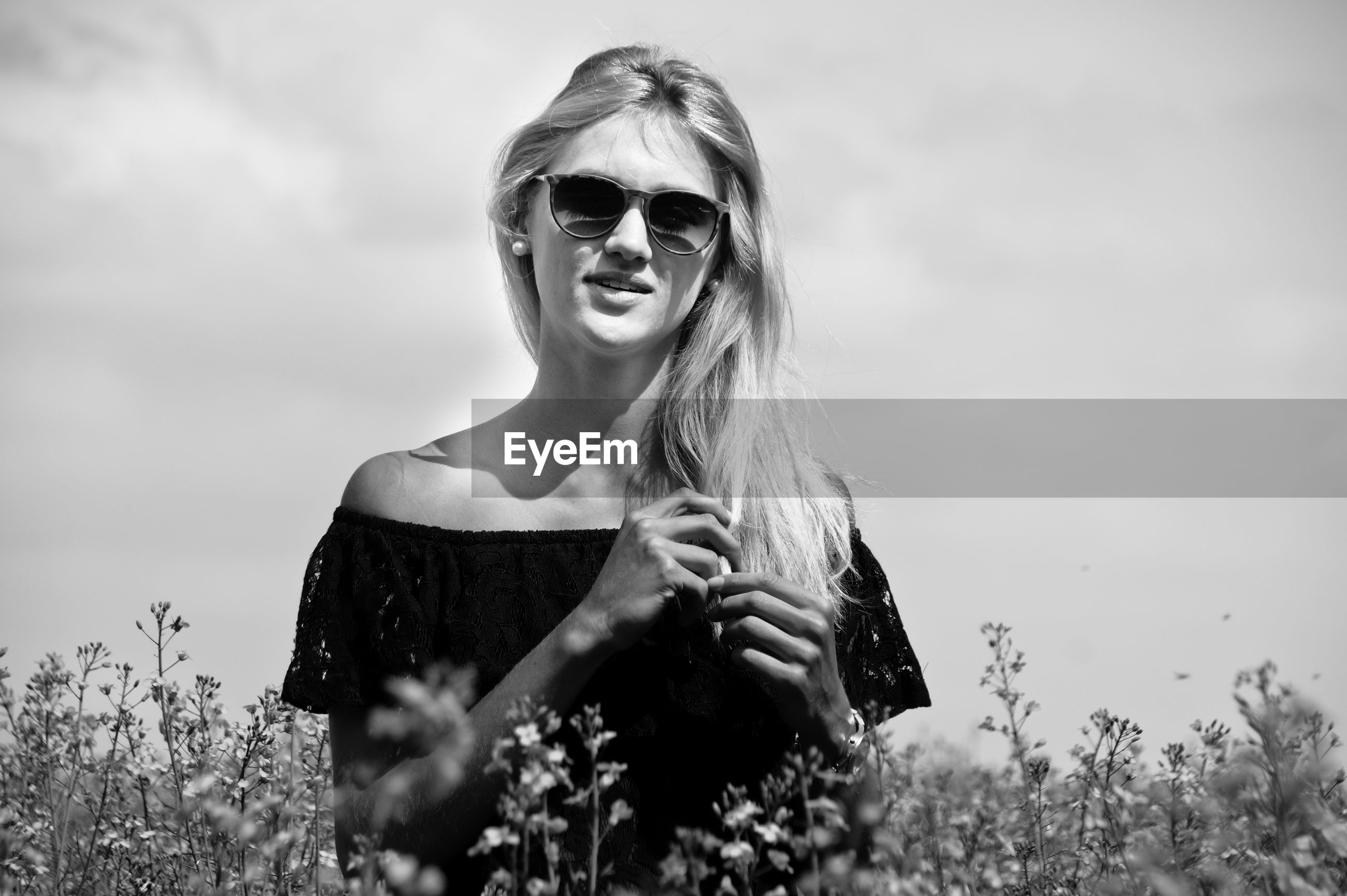 Portrait of young woman wearing sunglasses on field against sky