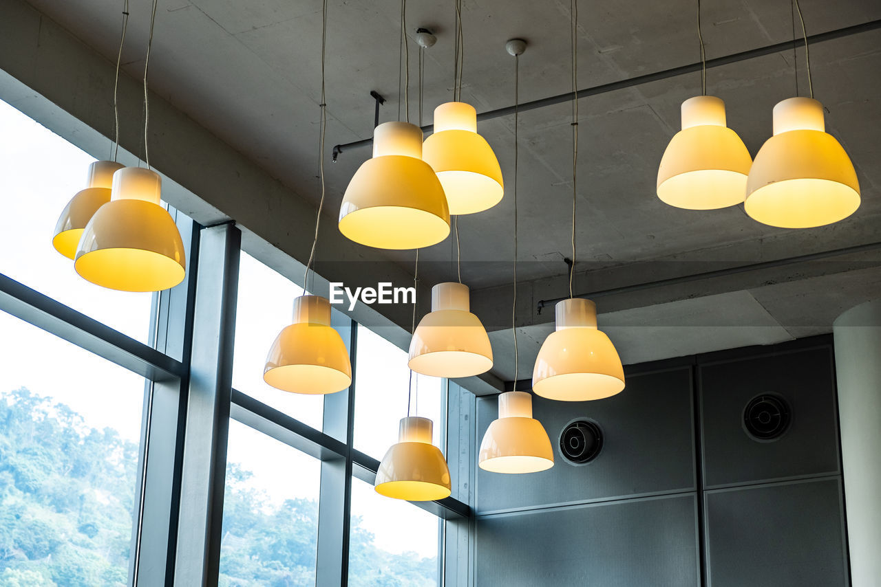 lighting equipment, ceiling, low angle view, no people, illuminated, indoors, yellow, pendant light, hanging, built structure, electricity, light, electric light, architecture, decoration, balloon, window, glowing, in a row, electric lamp, light fixture