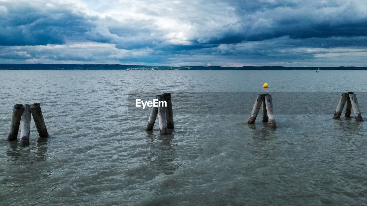 water, cloud - sky, sky, sea, waterfront, nature, scenics - nature, beauty in nature, tranquil scene, day, tranquility, horizon, horizon over water, post, outdoors, rippled, overcast, people, wooden post