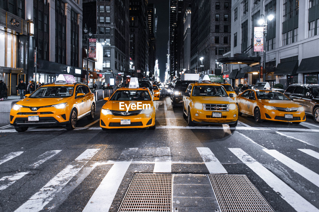 transportation, city, mode of transportation, architecture, taxi, car, street, building exterior, motor vehicle, built structure, yellow taxi, city life, road, traffic, yellow, city street, road marking, symbol, motion, marking, cityscape, no people, outdoors, office building exterior, skyscraper