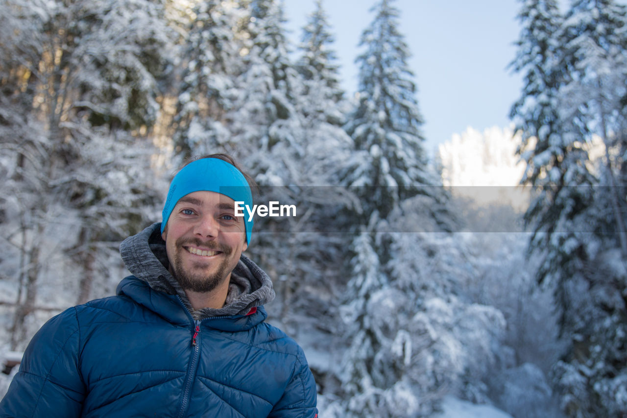 winter, snow, cold temperature, smiling, happiness, toothy smile, warm clothing, lifestyles, nature, looking at camera, portrait, mountain, tree, jacket, leisure activity, focus on foreground, one person, real people, outdoors, day, beauty in nature, ski holiday, cheerful, young adult, snowboarding, sky, adult, people