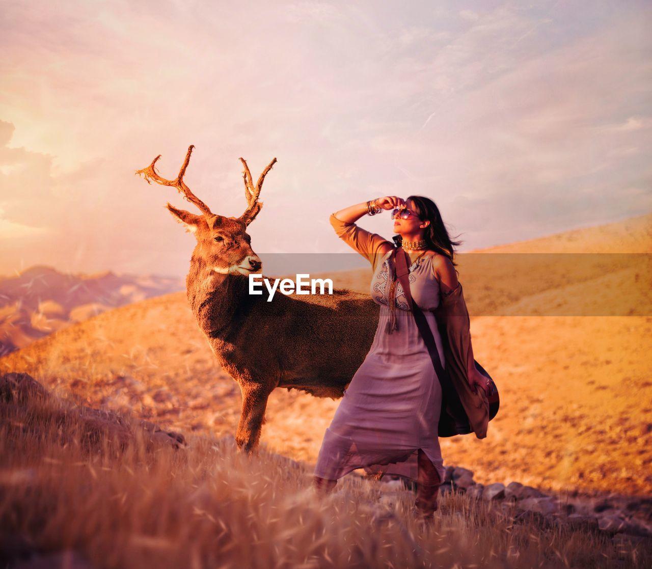 Woman standing by deer on land against sky
