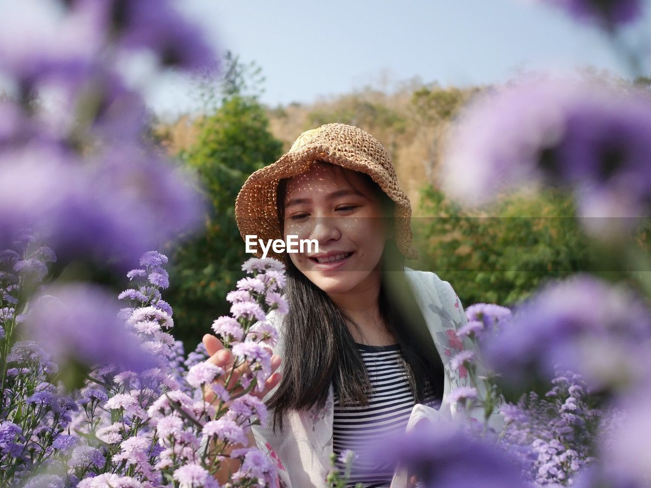 PORTRAIT OF SMILING YOUNG WOMAN WITH PURPLE FLOWER
