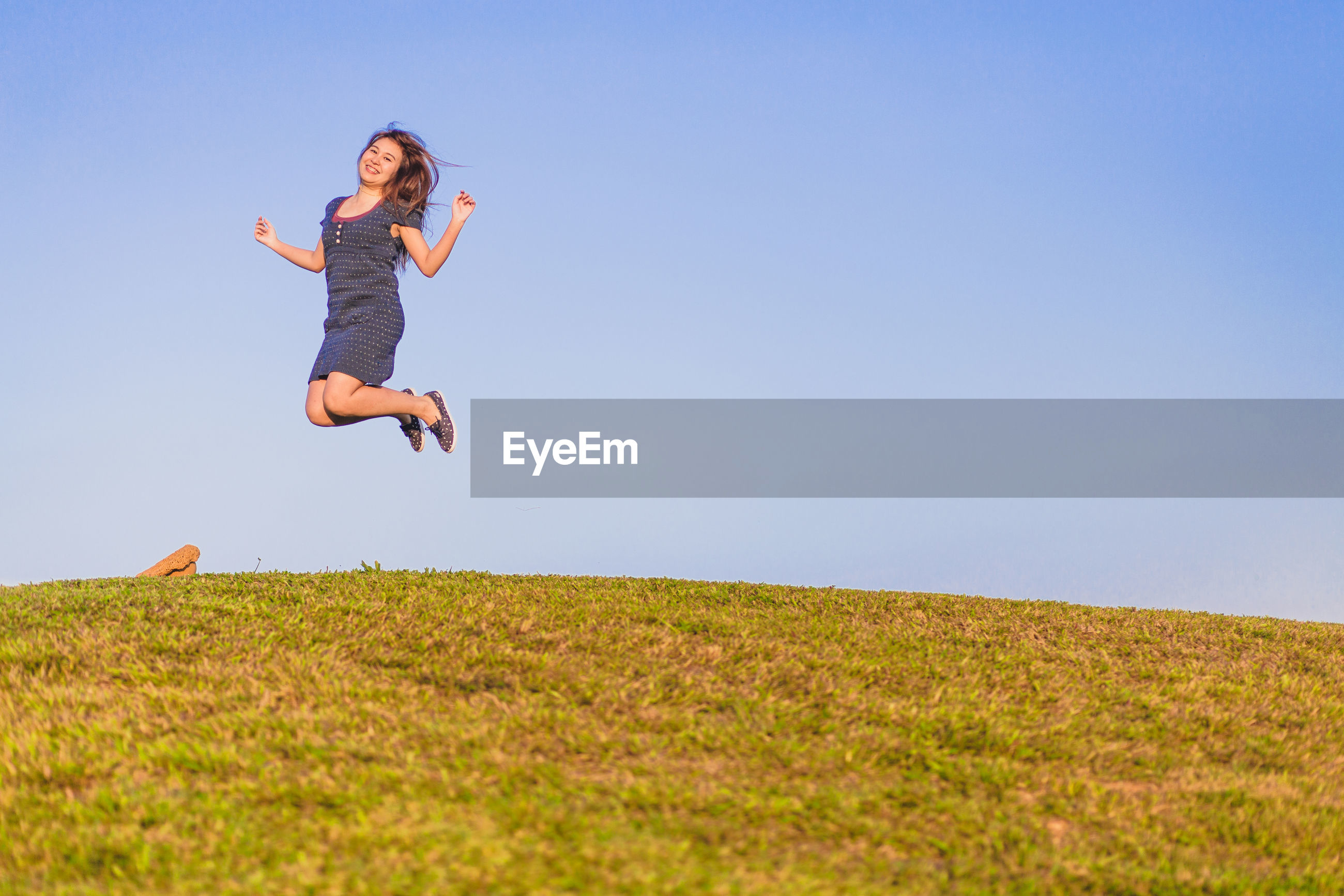 Full length of woman jumping over field against clear sky