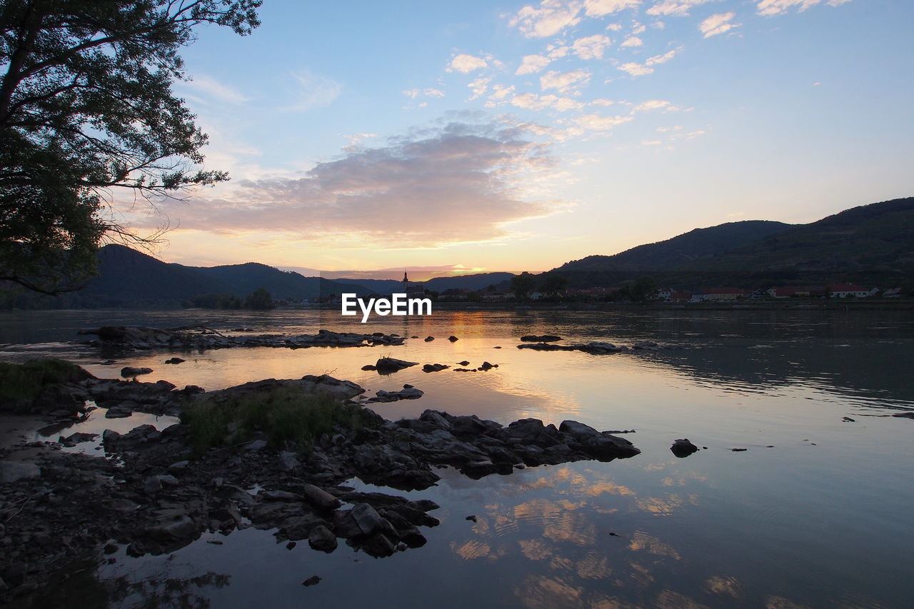 sky, water, beauty in nature, reflection, sunset, scenics - nature, cloud - sky, tranquil scene, tranquility, mountain, nature, lake, idyllic, non-urban scene, no people, waterfront, rock, solid, rock - object
