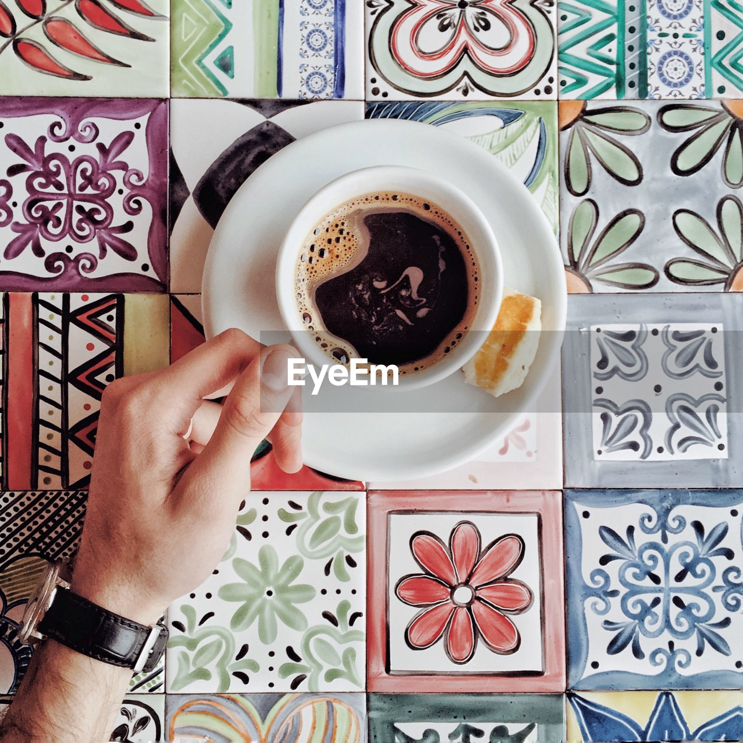 food and drink, human hand, coffee, mug, cup, hand, coffee - drink, coffee cup, one person, real people, directly above, human body part, holding, drink, refreshment, indoors, freshness, table, food, pattern, crockery, floral pattern, finger, tiled floor