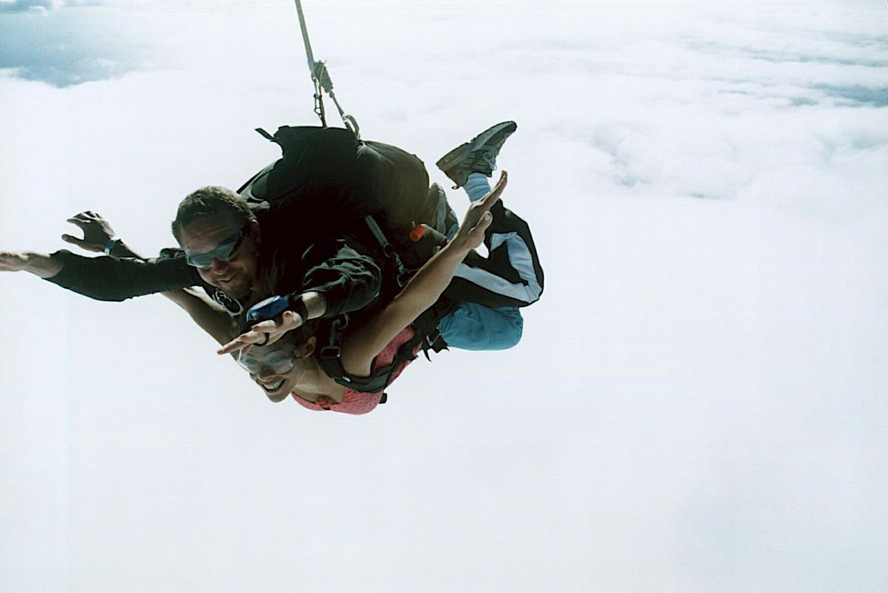 Mid Adult Man And Young Woman Skydiving In Sky