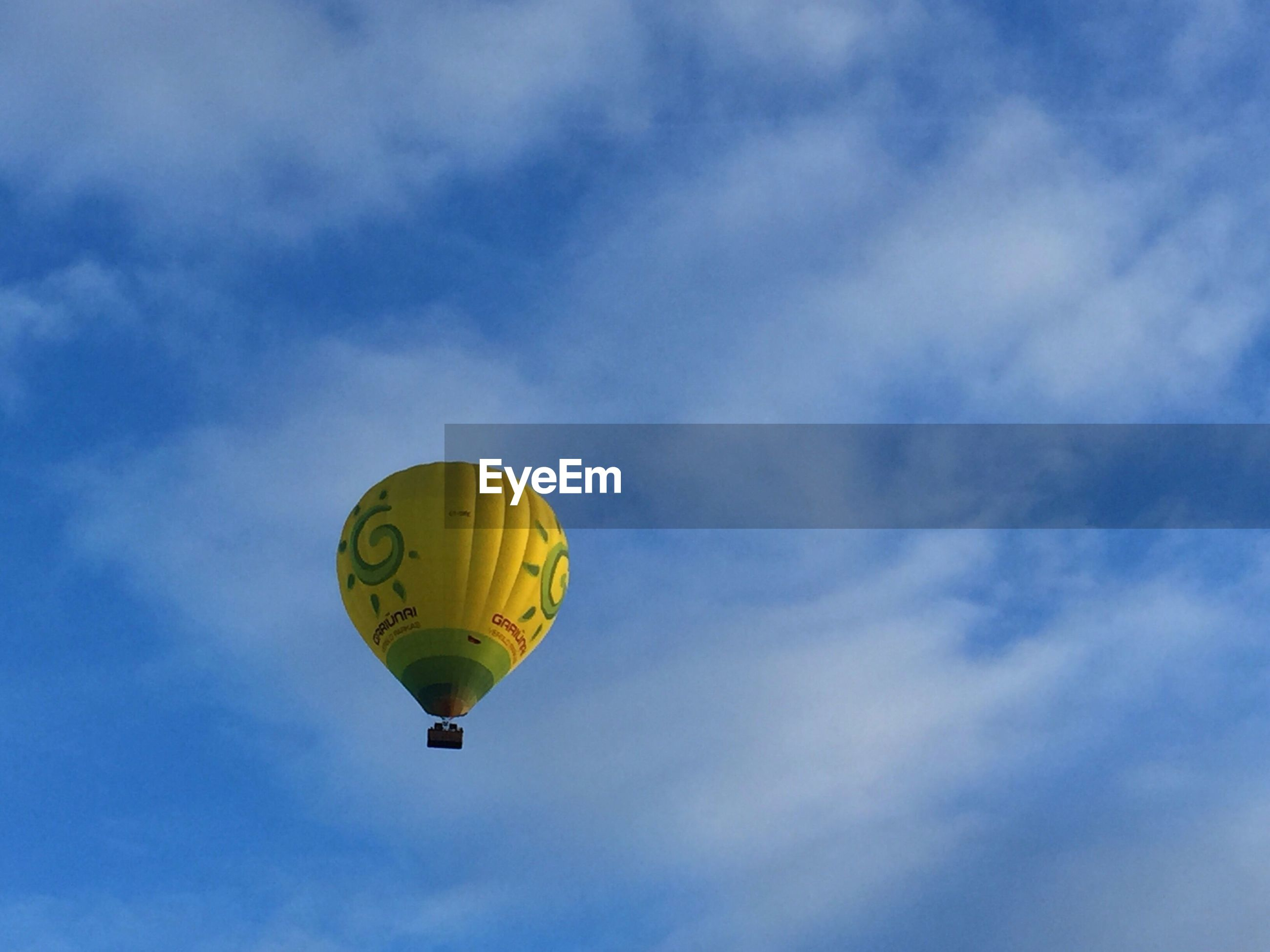 adventure, mid-air, sky, cloud - sky, hot air balloon, flying, parachute, outdoors, day, low angle view, leisure activity, real people, extreme sports, ballooning festival, yellow, multi colored, one person, people