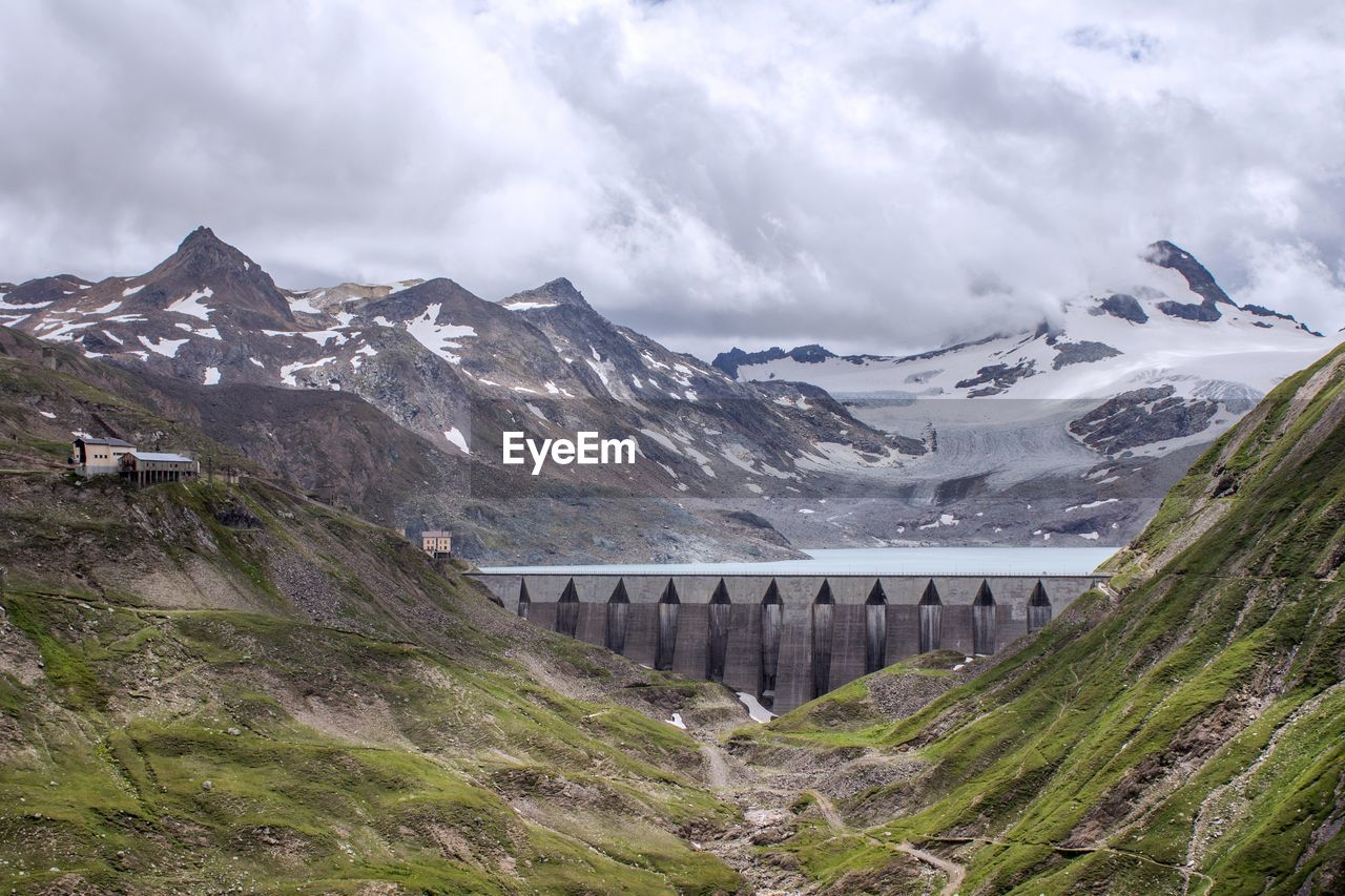 View Of Dam Amidst Snowcapped Mountains Against Cloudy Sky
