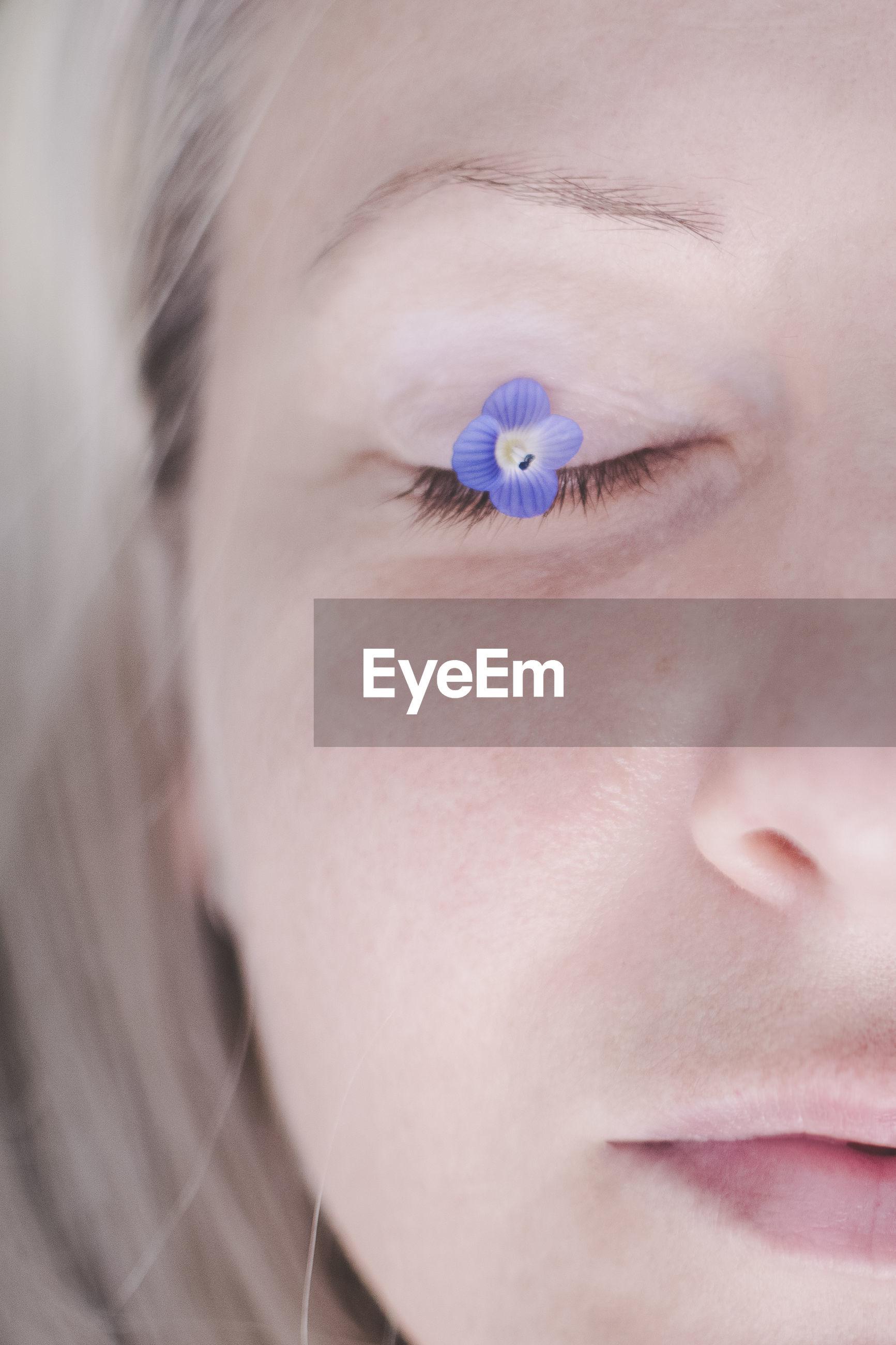 Purple flower on eye of woman