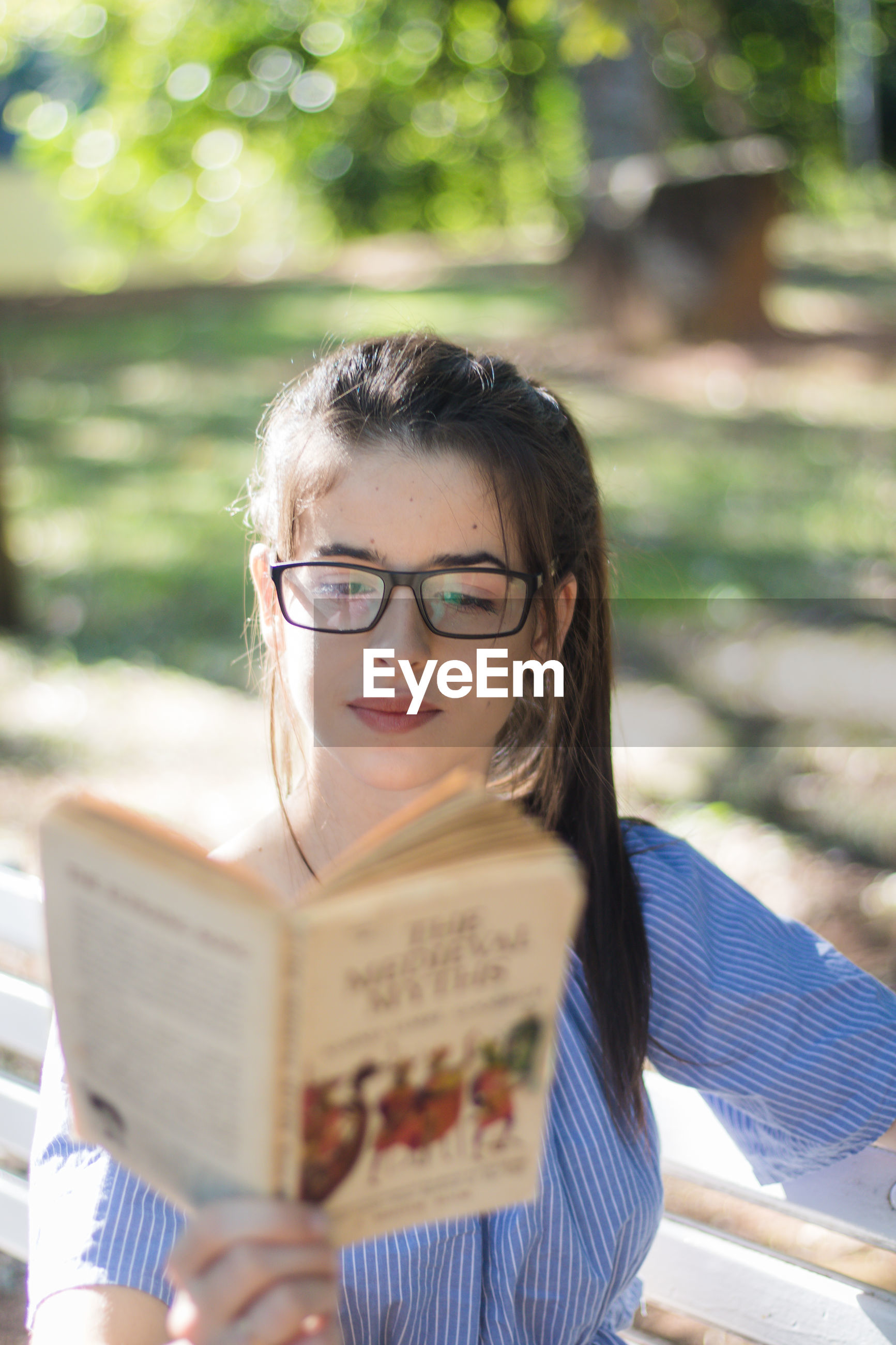 Young woman wearing eyeglasses reading book while sitting on bench at park