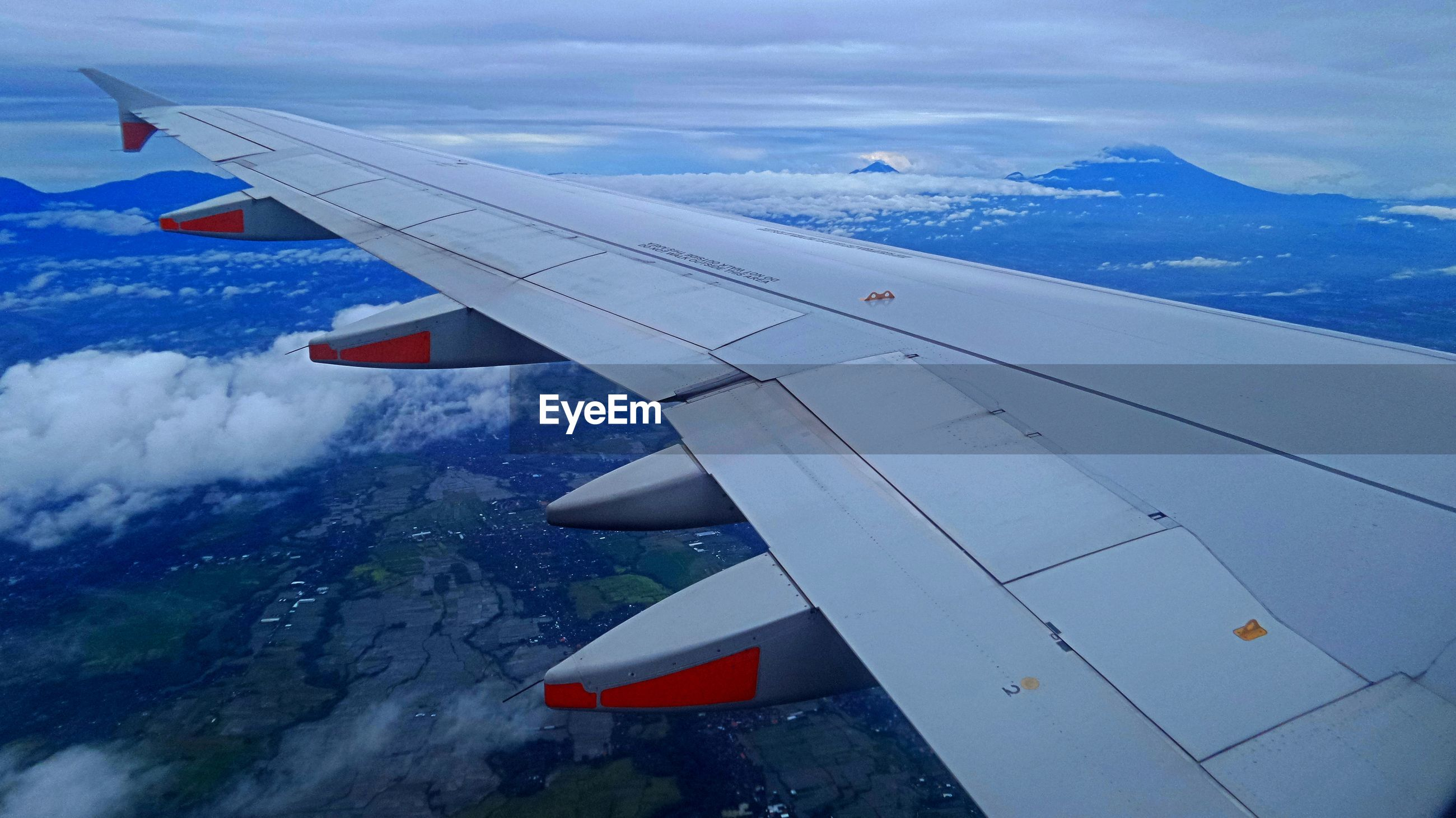 AIRPLANE WING OVER LANDSCAPE AGAINST SKY