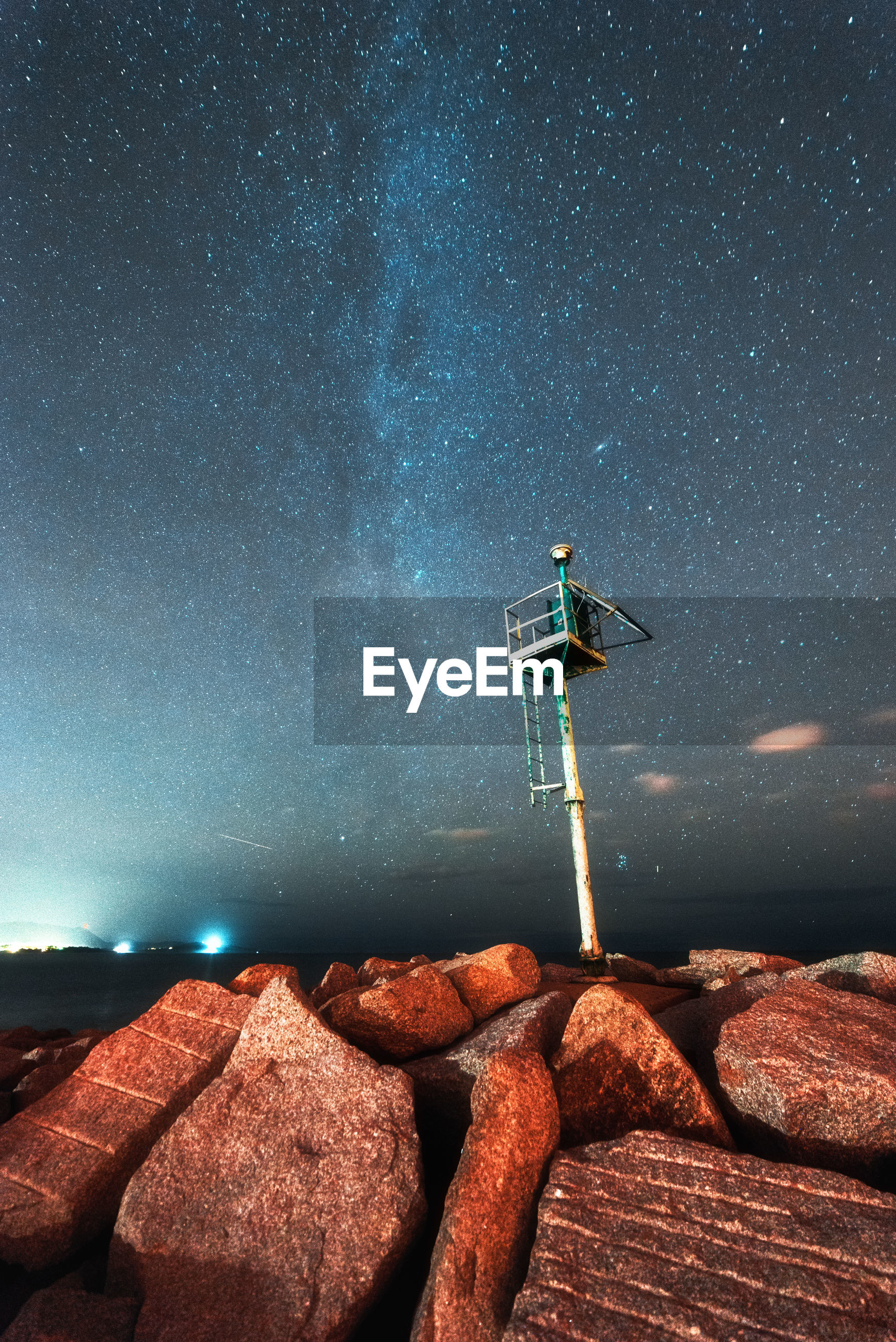 LOW ANGLE VIEW OF ROCKS AGAINST STAR FIELD AT NIGHT
