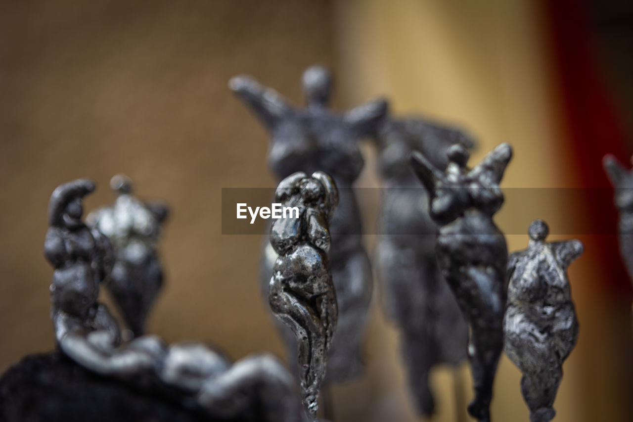 focus on foreground, sculpture, representation, close-up, no people, art and craft, statue, creativity, human representation, indoors, day, craft, architecture, mammal, selective focus, metal, nature, silver colored