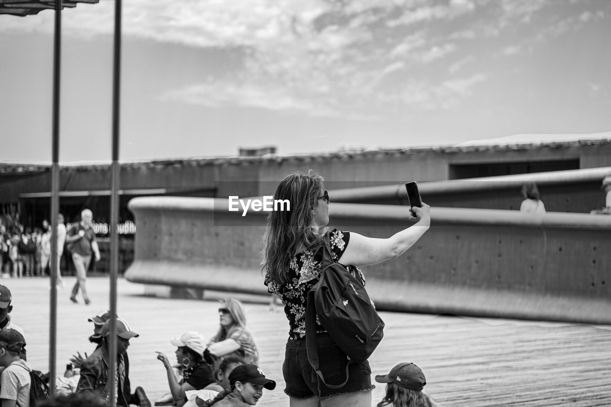 REAR VIEW OF WOMAN PHOTOGRAPHING WITH UMBRELLA ON RAILING