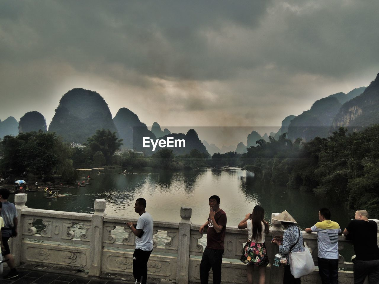 PEOPLE STANDING BY MOUNTAINS AGAINST SKY