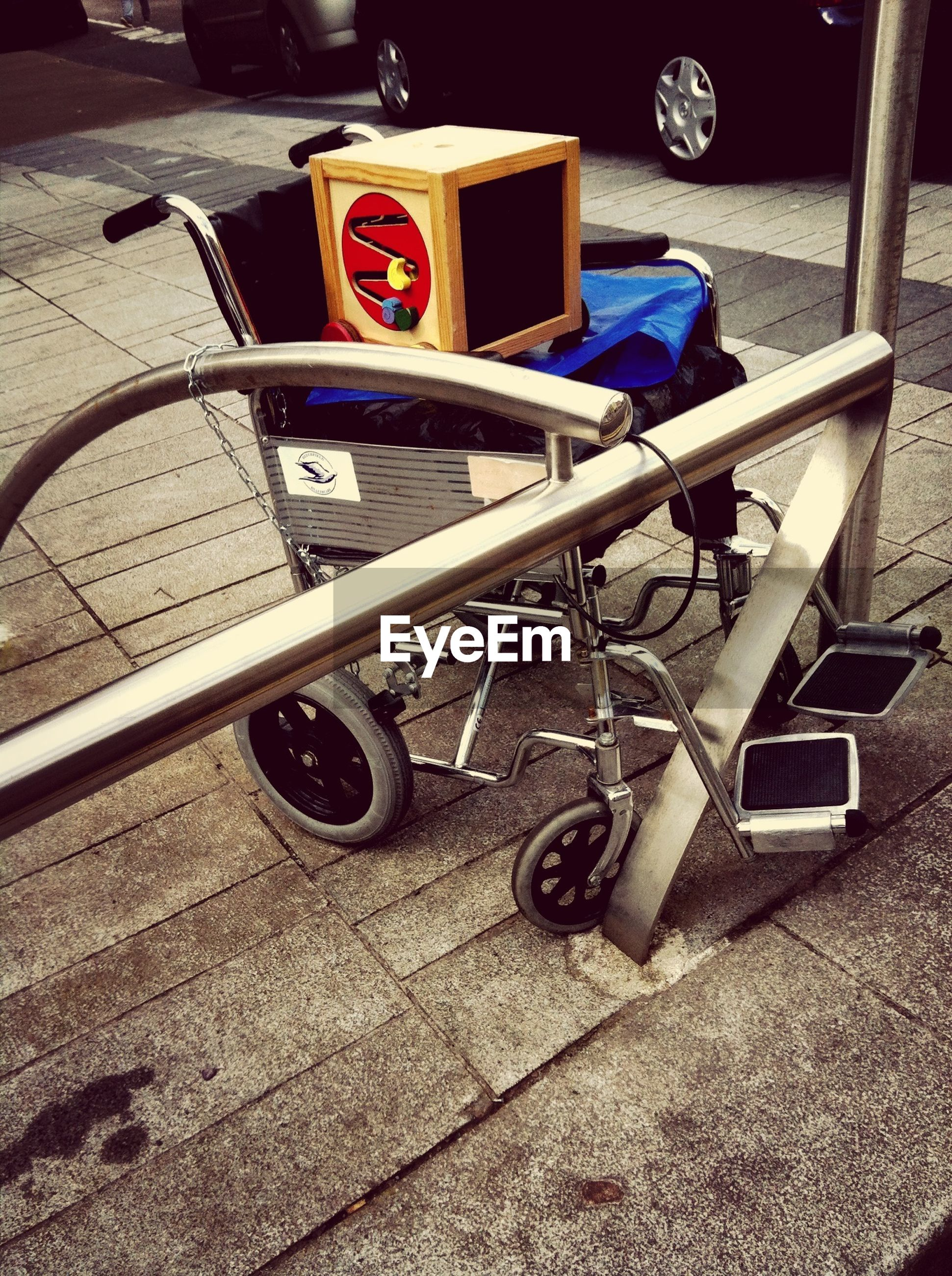 High angle view of wheelchair on street with box
