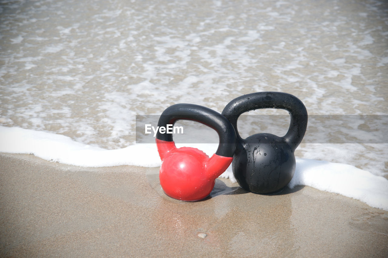 High Angle View Of Kettlebells At Beach
