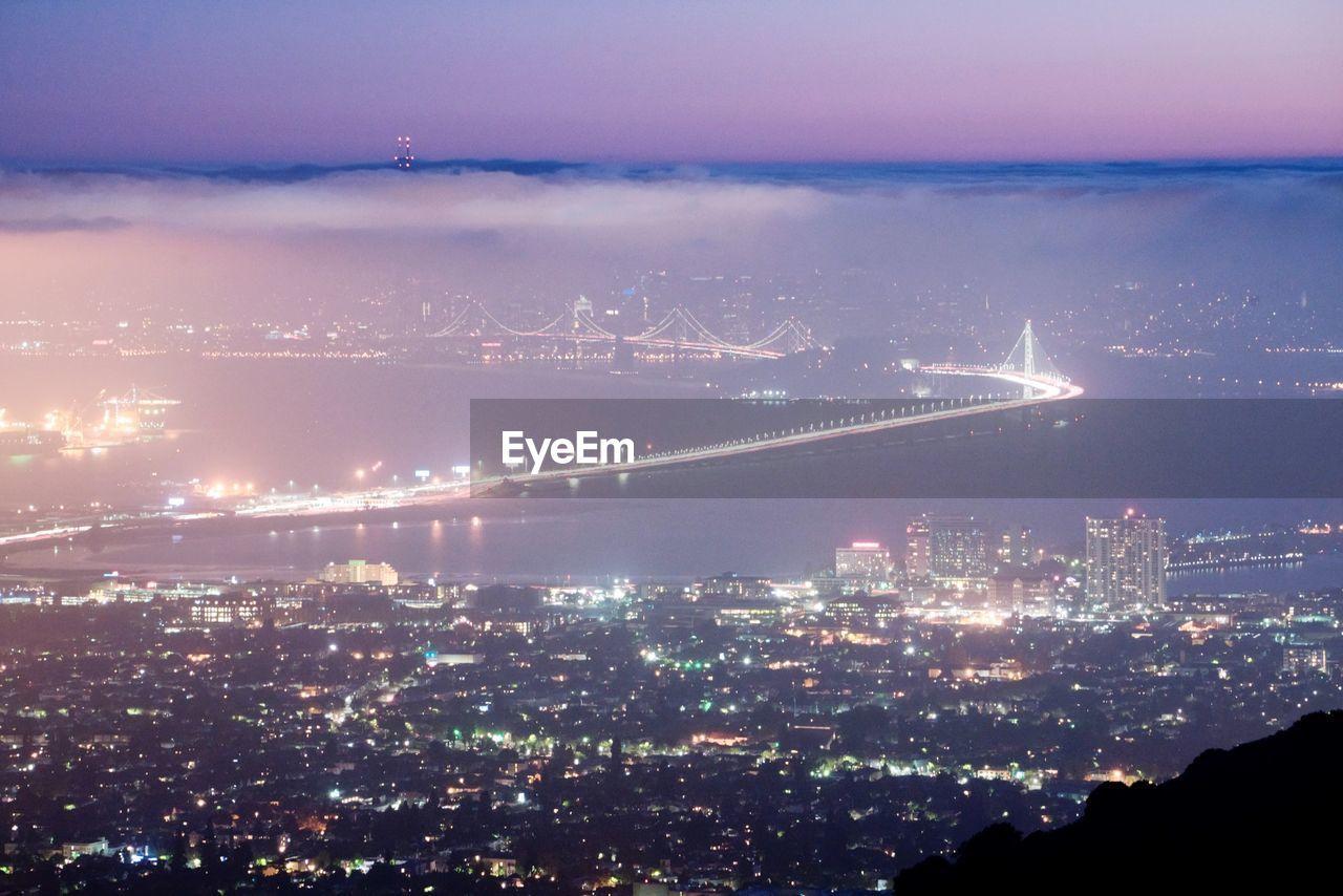 Aerial view of illuminated bay bridge and cityscape at night