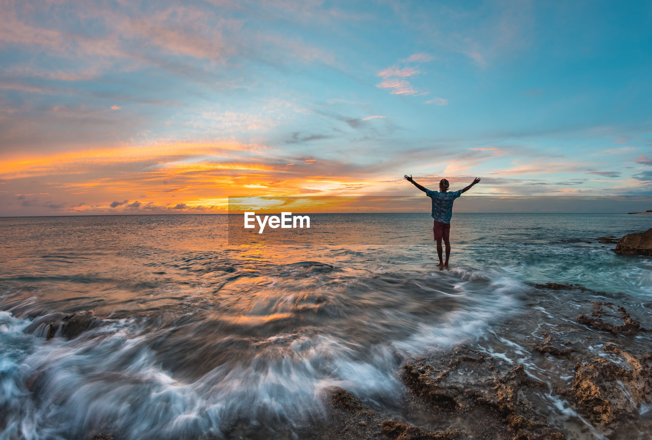 sky, sea, human arm, sunset, cloud - sky, beauty in nature, water, limb, scenics - nature, arms raised, one person, horizon over water, leisure activity, real people, lifestyles, rock, horizon, rear view, rock - object, arms outstretched