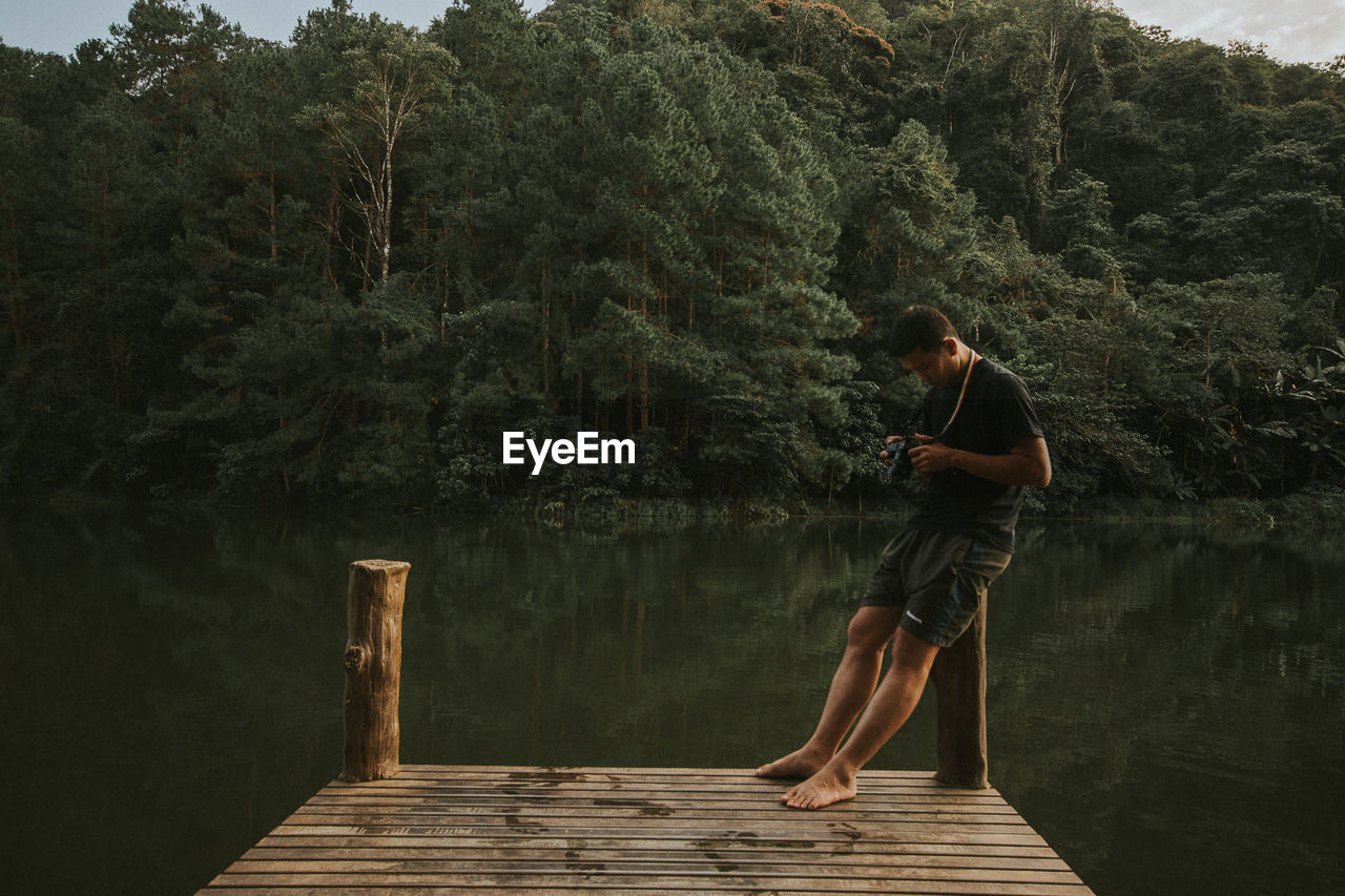 Man Holding Camera While Sitting On Bollard Against Lake