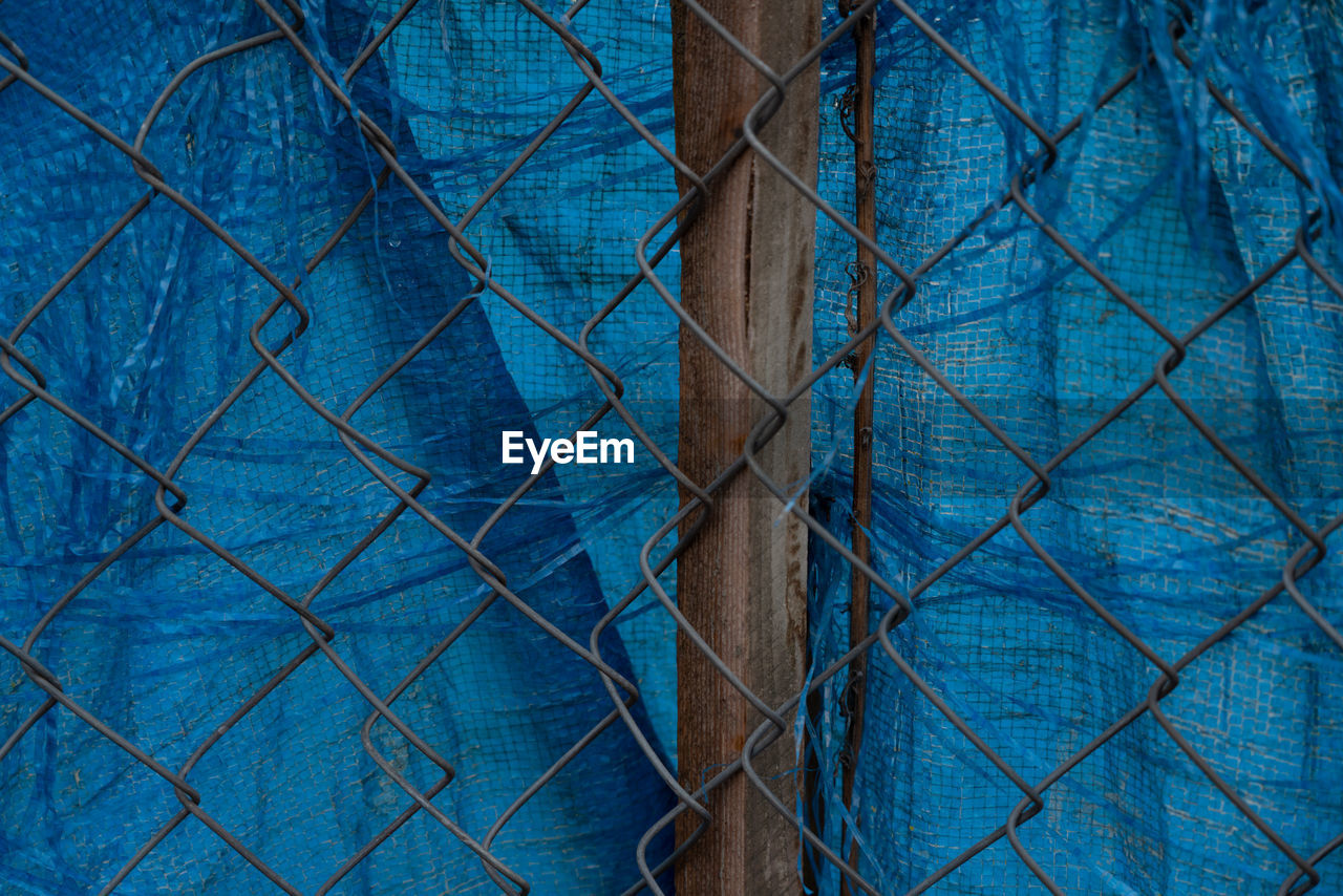 CLOSE-UP OF BLUE CHAINLINK FENCE