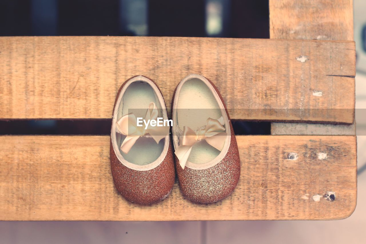 Directly above shot of small sandals on wooden table