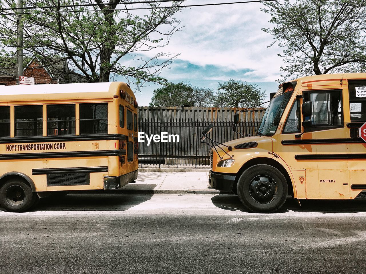mode of transportation, transportation, land vehicle, day, tree, motor vehicle, yellow, street, bus, plant, public transportation, stationary, city, road, outdoors, architecture, parking, nature, car, school bus, no people