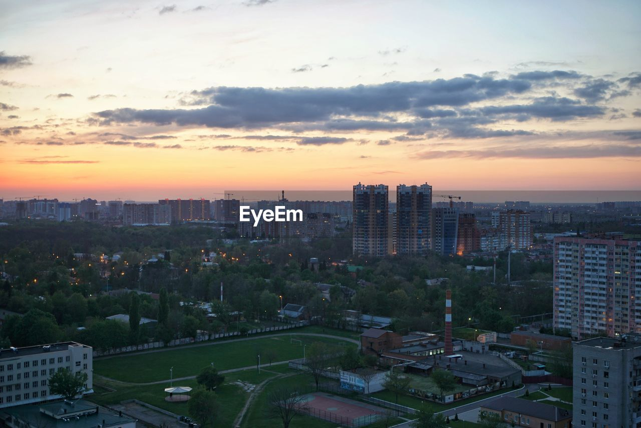 architecture, cityscape, building exterior, city, built structure, skyscraper, sky, sunset, cloud - sky, modern, no people, outdoors, urban skyline, travel destinations, growth, nature, tree, day