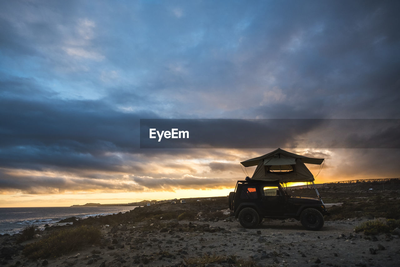 Tent On Vehicle At Beach Against Cloudy Sky