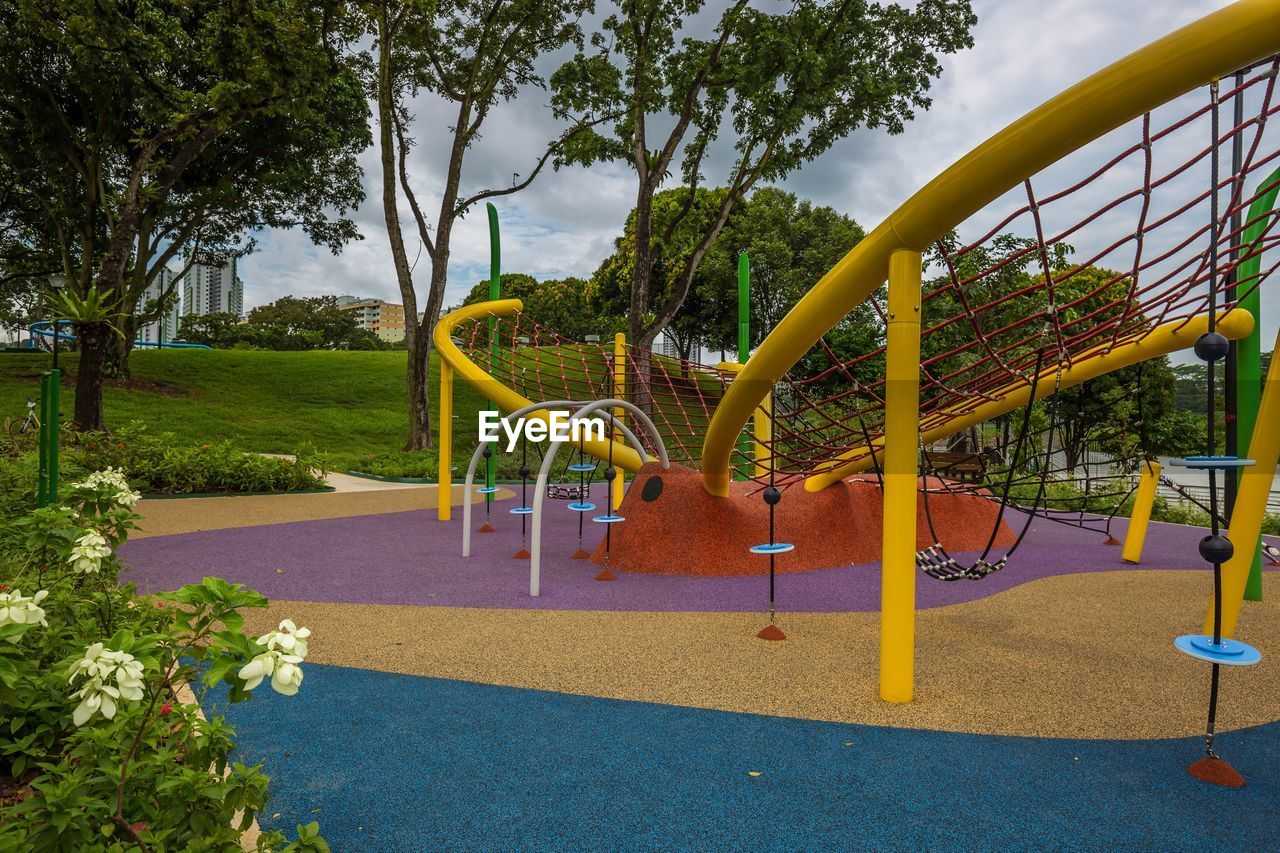 plant, playground, tree, park, childhood, nature, park - man made space, slide, day, empty, absence, outdoors, yellow, slide - play equipment, growth, sky, outdoor play equipment, sunlight, beauty in nature