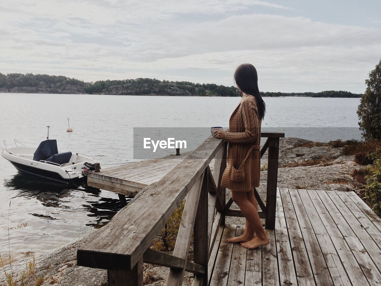 REAR VIEW OF WOMAN LOOKING AT VIEW OF LAKE AGAINST SKY