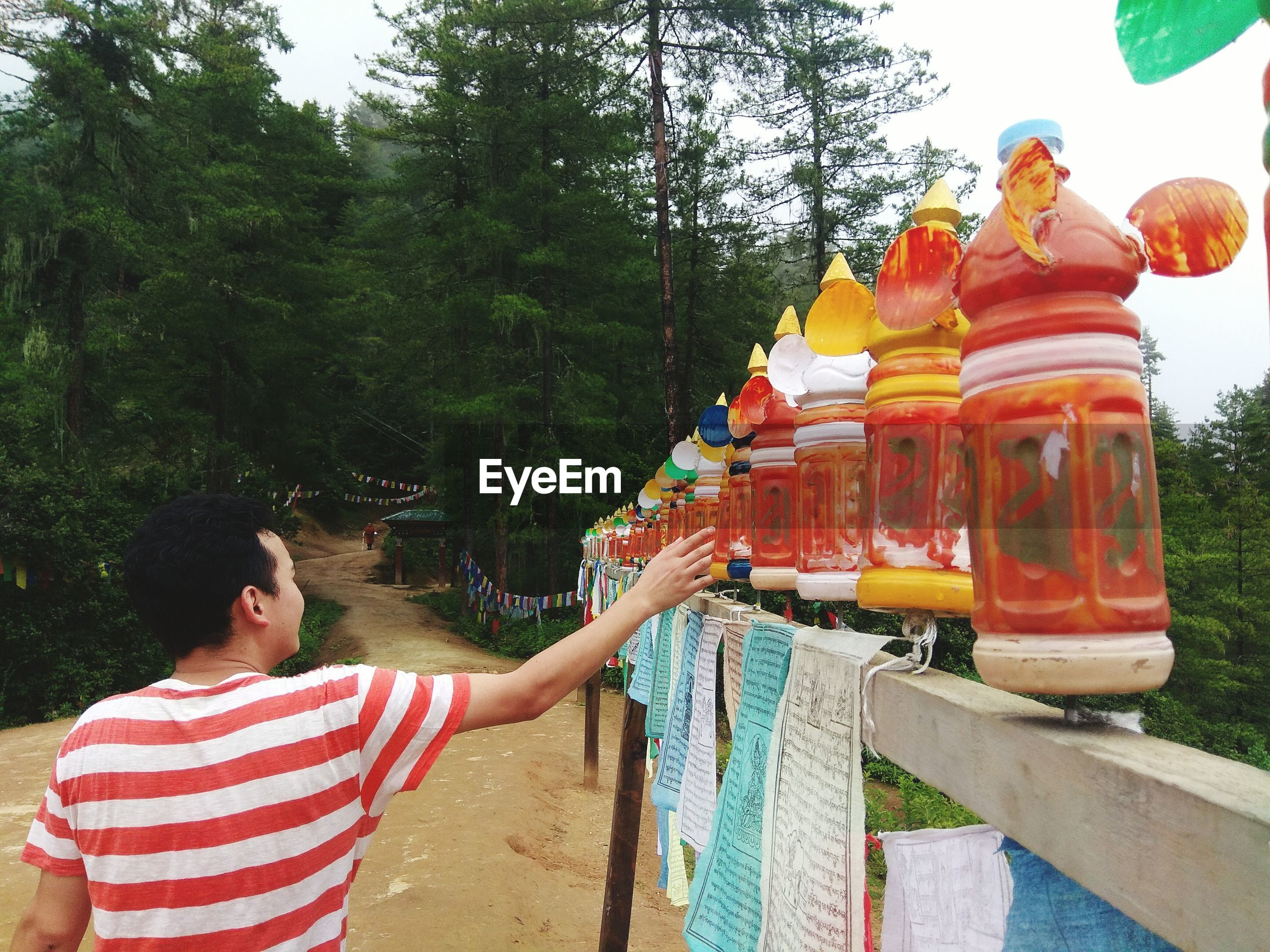Rear view of man rolling prayer wheels at temple