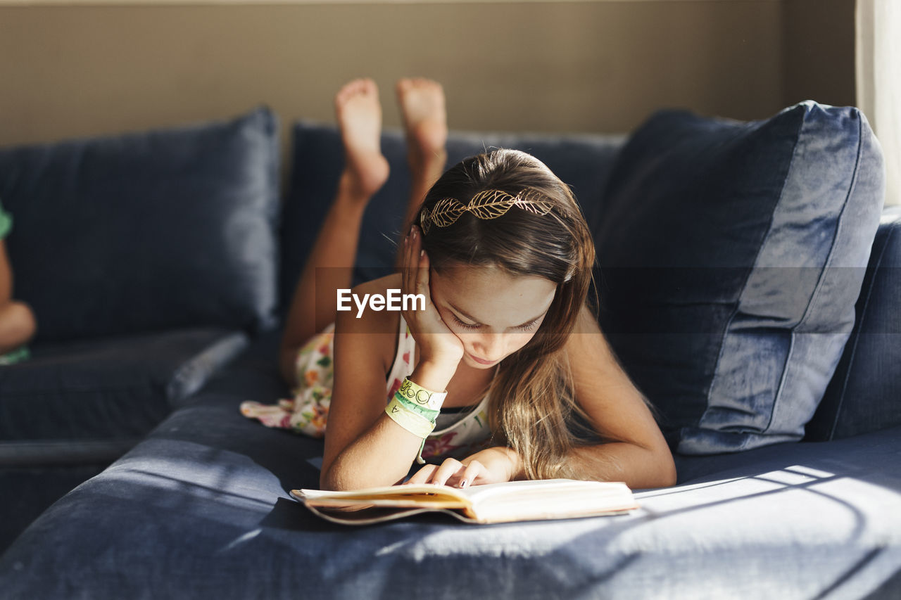 YOUNG WOMAN LYING ON BOOK