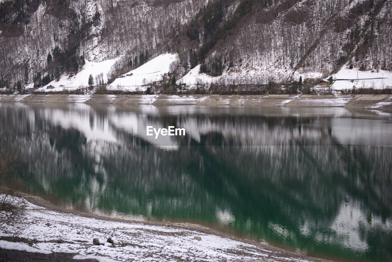 water, tree, reflection, cold temperature, scenics - nature, beauty in nature, winter, tranquility, nature, snow, no people, tranquil scene, plant, day, lake, waterfront, non-urban scene, outdoors