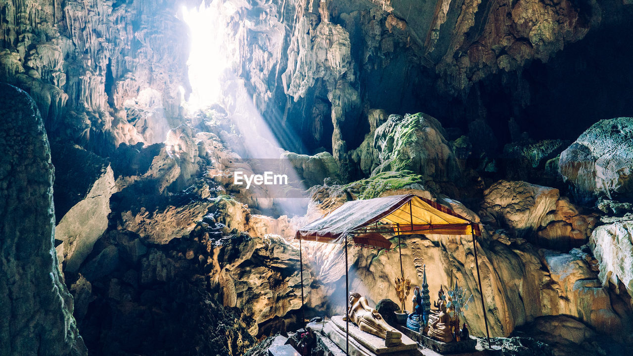 Sunlight streaming on buddha statue in cave