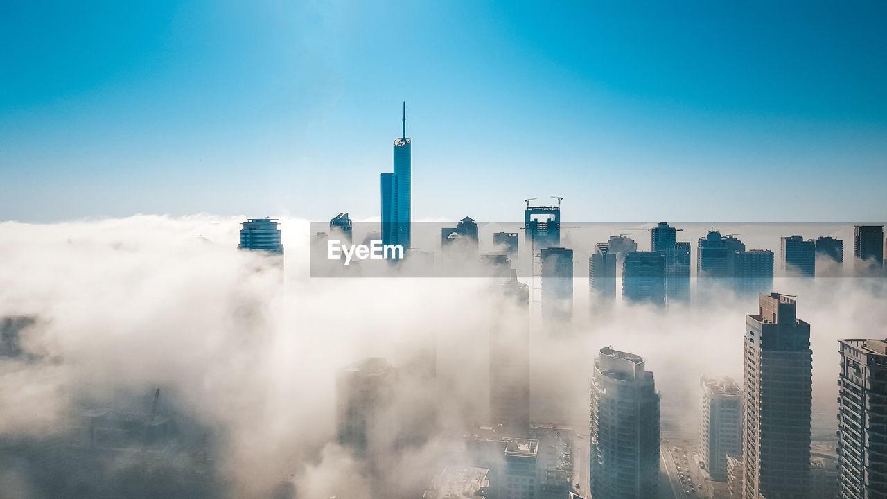 Panoramic view of dubai marina buildings in fog against cloudy sky