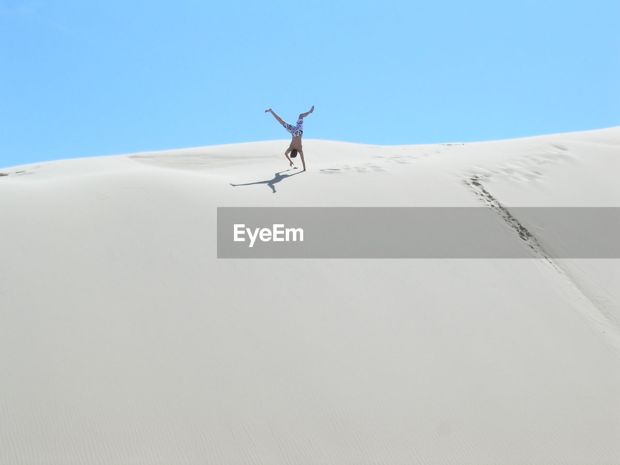 Low Angle View Of Man Practicing Handstand On Sand Dune
