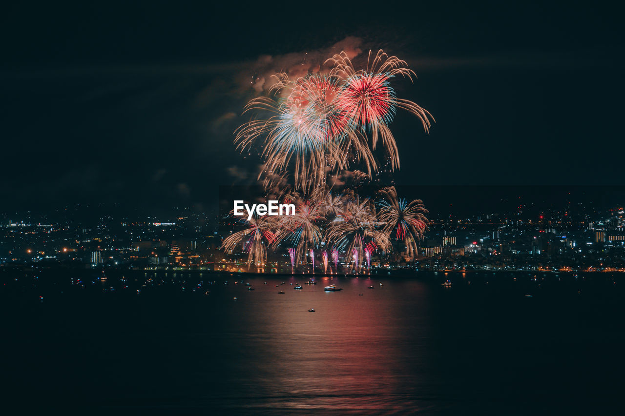 Firework display over illuminated city against clear sky at night