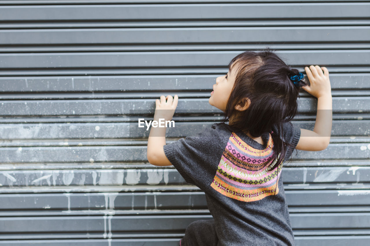 Rear View Of Girl Playing By Closed Shutter